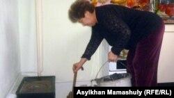 Женщина топит печку. Иллюстративное фото.