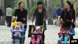 Балалармен серуендеп жүрген әйелдер. Пекин, 5 сәуір 2011 жыл.