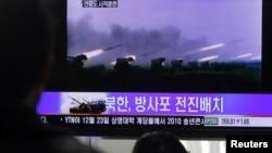 Оңтүстік Корея тұрғындары Солтүстік Корея қарулы күштері туралы бейнематериалды қарап тұр. Сеул, Оңтүстік Корея. 20 желтоқсан 2010 ж.