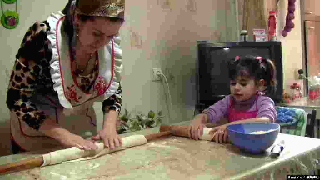 Shahnoz Komilzoda preparing food with her child in their kitchen in Dushanbe