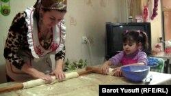 Таджикская бизнес-леди Шахноз Комилзода учит свою дочь Мумтаз готовить манты. Душанбе, 5 марта 2013 года