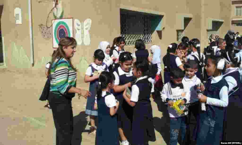 A teacher and her students in the courtyard of their school in Baghdad