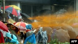 Жена показва неприличен жест, докато полицията използва водно оръдие срещу протестиращите
