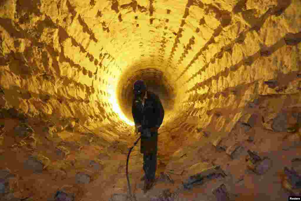 An Iraqi worker operates a drill during a cleanup of the furnace pipes at a cement plant in Najaf, south of Baghdad. (Reuters/Ahmad Mousa)