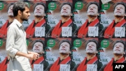 A Pakistani man walks past electoral posters of Pakistani politician and former cricketer Imran Khan, in Karachi.
