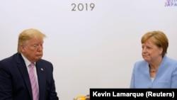 Президент США Дональд Трамп (слева) и канцлер Германии Ангела Меркель на саммите «Большой двадцатки» в Осаке. 28 июня 2019 года.