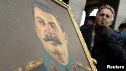 Мужчина с портретом Иосифа Сталина в его родном городе Гори, Грузия, 21 декабря 2011 года.