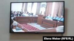 Монитор показывает участников судебного разбирательства по делу бывшего премьер-министра Серика Ахметова, обвиняемого в коррупции. Караганда, 20 октября 2015 года.