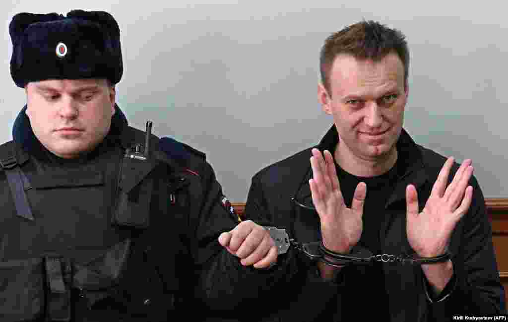 Kremlin critic Aleksei Navalny, who was arrested during a March 26 anticorruption rally, gestures as he wears two pairs of handcuffs during an appeal hearing at a court in Moscow. A Russian court on March 27 sentenced him to 15 days behind bars after ruling that he had resisted police. (AFP/Kirill Kudryavtsev)