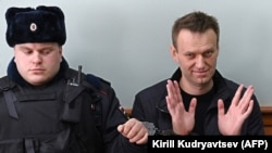 Kremlin critic Aleksei Navalny (right) gestures during his appeal hearing at a court in Moscow on March 30.