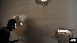 Ҳалаб шаҳрининг Салоҳиддин туманидаги бино девори туйнугидан ҳукумат аскарларини кузатаётган исёнчи, 2013 йил 16 феврал.