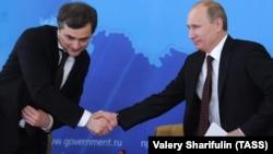 Владимир Путин, в бытность премьер-министром России, жмет руку своему заместителю Владиславу Суркову. 12 февраля 2012 года.