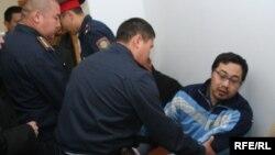 Полицейлер Ермек Нарымбаевты сот залынан әкетіп барады. Алматы, 14 маусым 2010 жыл.