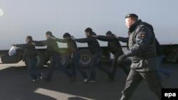 Polisiýa Birýulýowo raýonynda gök önümlerini satýan bazada migrantlary saklaýar, Moskwa, 14-nji oktýabr, 2013.