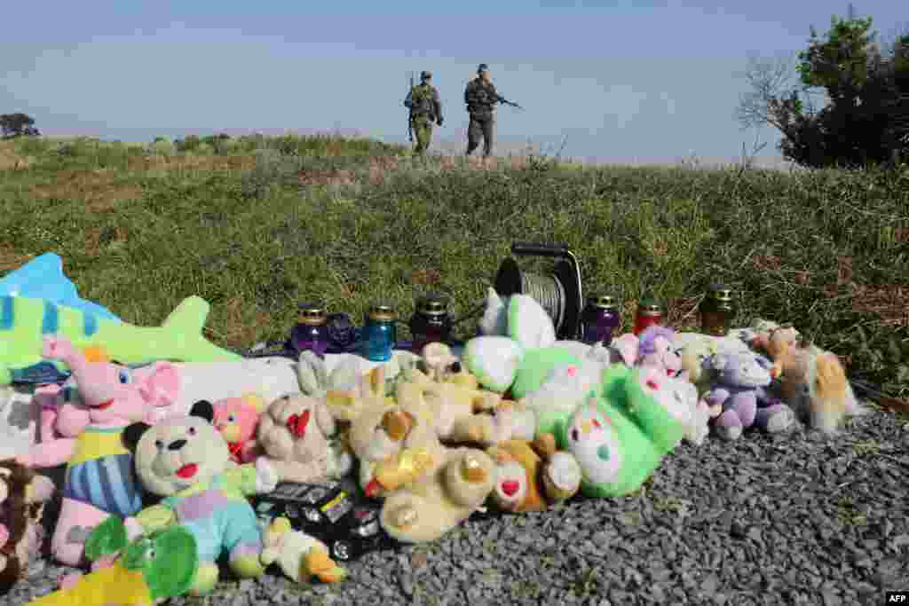 Pro-Russian armed rebels walk near stuffed animals and candles left at the site of the MH17 flight crash in Ukraine's Donetsk region. (AFP/Aleksey Filippov)