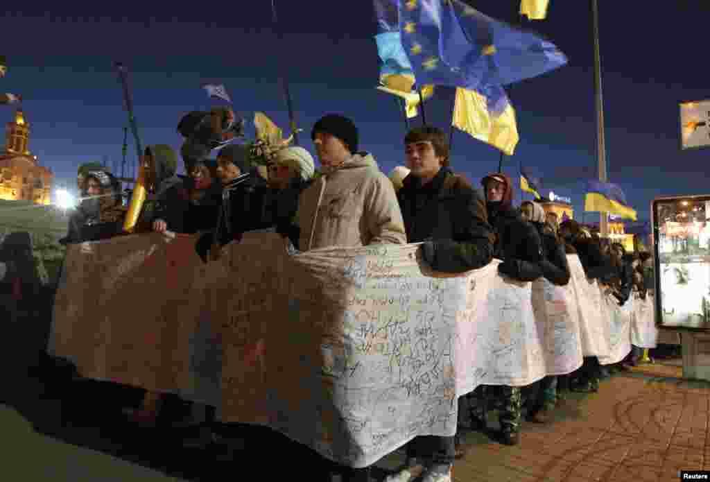 Tələbələr prezident Viktor Yanukovich-ə ünvanladıqları 500 metr uzunluğunda etiraz məktubunu nümayiş etdirirlər. Kiyev, 27 noyabr 2013