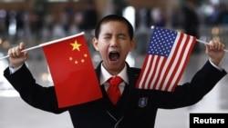АКШ менен Кытай тууларын көтөргөн кытайлык окуучу. Бээжин, 2012-жыл.