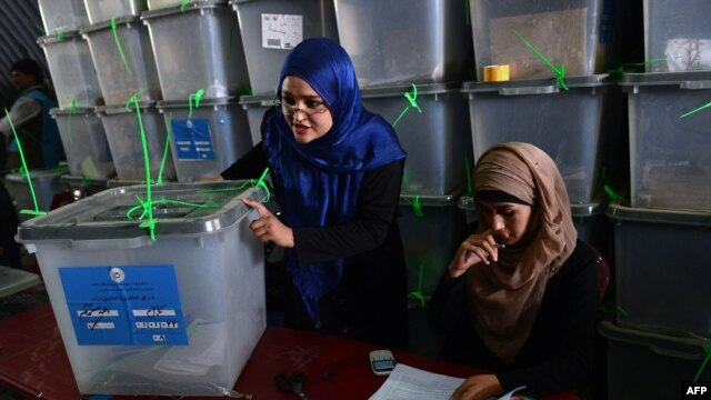 Afghan election commission workers prepare to cut open the seals to a box containing ballot papers for an audit of the presidential runoff votes at a counting center in Kabul on July 17.