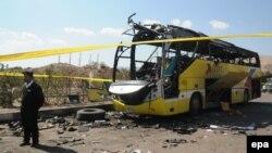 شرطي مصري يقف أمام الحافلة التي تعرض للتفجير
