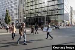 """Stojčić s natpisom """"bol za domom"""" na ulicama Berlina."""