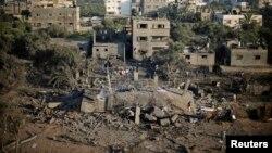 Palestinezët afër një shtëpie për të cilën policia thotë se është shkatërruar nga sulmet ajrore izraelite më 8 korrik