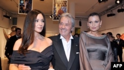 "Lola Karimova-Tillyaeva (right) with French actor Alain Delon and Italian actress Monica Bellucci (left) pose before attending a gala dinner for the launch of the charity fund ""Uzbekistan 2020"" in Paris in 2009."