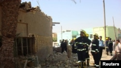 رجال أمن وعمال إنقاذ في موقع الإنفجار بالديوانية