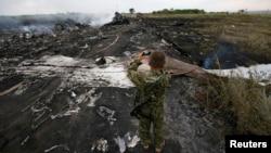 """Вооруженный пророссийский сепаратист снимает на фото на месте крушения малайзийского """"Боинга-777. Донецкая область, 17 июля 2014 года."""