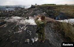 Пророссийский боевик фотографирует место крушения лайнера Boeing 777 авиакомпании Malaysia Airlines. Донецкая область, 17 июля 2014 года.