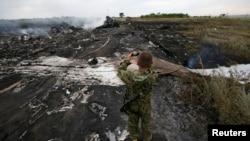 Një pjesëtar i separatistëve prorusë e fotografon vendin e rrëzimit të aeroplanit