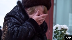 A woman cries as she lays flowers at an impromptu memorial outside a Moscow theater that housed the Aleksandrov Ensemble. Dozens of members of the renowned choir died when the military plane they were traveling on crashed into the Black Sea on December 25.