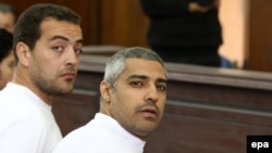 Al-Jazeera journalists Mohammed Fahmy and Baher Mahmoud (left) on trial in Cairo in March