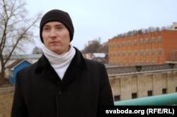 Зьміцер Казлоў. Ззаду — ізалятар часовага ўтрыманьня, у якім ён адседзеў амаль месяц