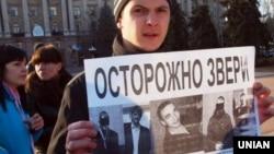 Плакат з портретами підозрюваних в зґвалтуванні 18-річної Оксани Макар на плакаті одного з учасників мітингу у Миколаєві, 15 березня