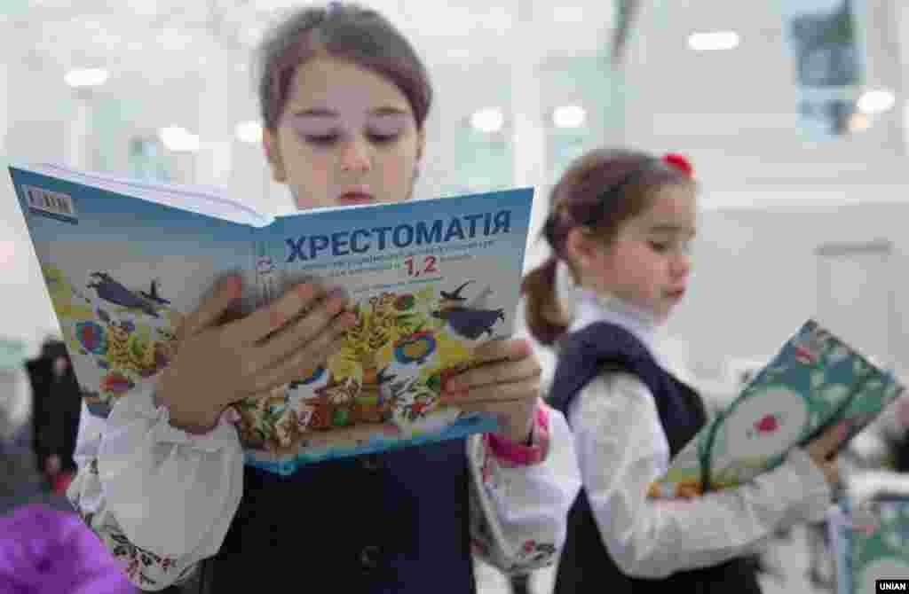 Дівчата роздивляються Хрестоматії сучасної дитячої літератури для 1-2 класів під час презентації підручників у Києві, 16 грудня 2016 року