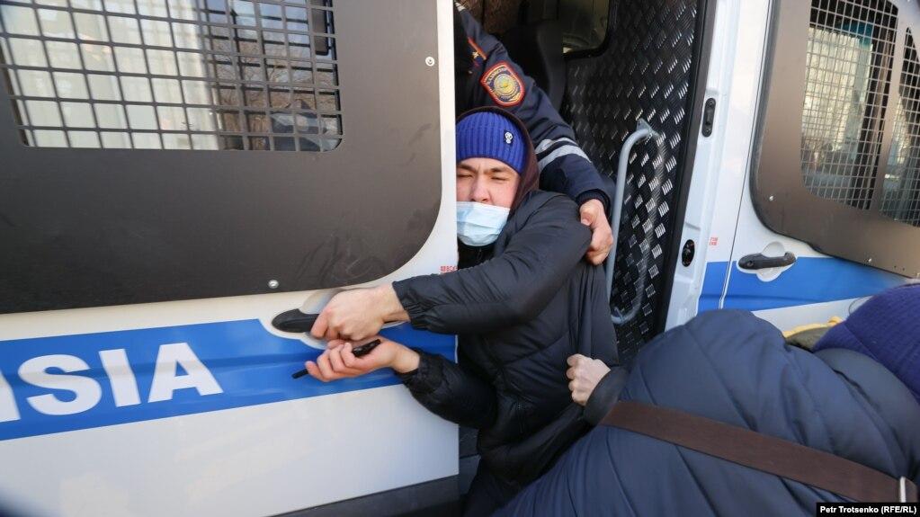 Задержанного на месте протеста полиция затаскивает в автозак. Алматы, 10 января 2021 года.
