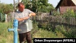 Житель села Степное Шортандинского района Акмолинской области набирает воду из колонки.