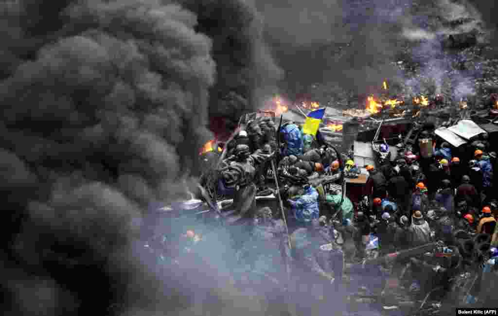 Protesters stand behind burning barricades during a face-off against police in Kyiv on February 20.