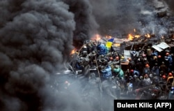 Antigovernment protesters stand behind burning barricades during a face-off against police in Kyiv on February 20, 2014.