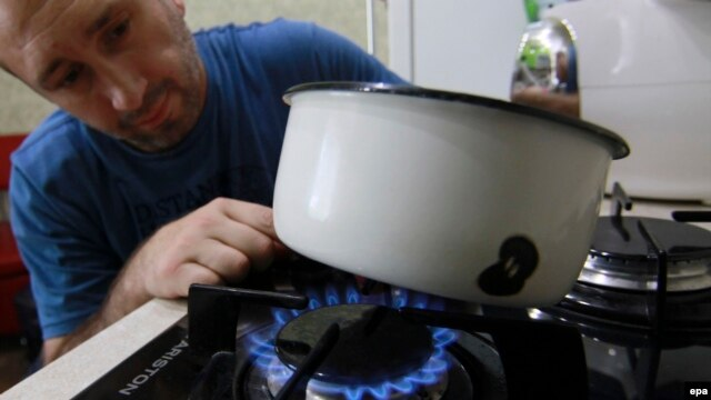 A man cooks on a gas stove in Donetsk, Ukraine.