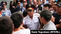 Полицейские сдерживают толпу родственников заключенных алматинской тюрьмы, которые требовали встречи с родными. Алматы, 30 июля 2010 года.