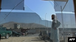 An Afghan man looks on while seen through broken glass at a shop at the site of a suicide attack in Kabul, July 22, 2014.