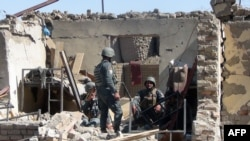 Afghan policemen at the site of a suicide bombing attack on the police headquarters in the s eastern Gardez city.
