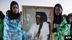 Women from the nomadic Tuareg tribe in traditional dress hold a portrait of Libyan leader Muammar Qaddafi during the 16th International Ghat Festival in southwest Libya in February 2010.