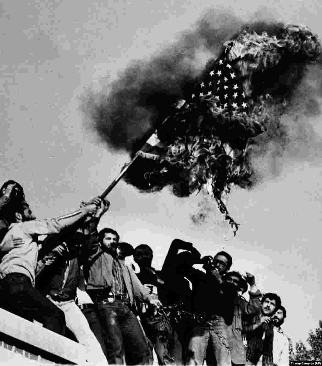 9 листопада 1979 року. Учасники протесту спалюють американський прапор на стіні посольства США в Тегерані. Через кілька тижнів після того, як шах залишив країну, в Іран із 14-річного заслання в Парижі повернувся аятола Рухолла Хомейні. У березні 1979 року в під час референдуму переважна більшість іранців висловилися за усунення монархії і перехід до ісламській держави