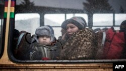 A woman and a young boy sit on a bus as they wait to flee heavy fighting in eastern Ukraine earlier this year.