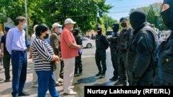 Прибывшие на объявленный двумя оппозиционными группами митинг граждане напротив сотрудников спецподразделения полиции. Алматы, 6 июня 2020 года.