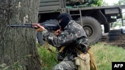 A pro-Russian militant takes aim at a checkpoint in the eastern city of Slovyansk on June 3.