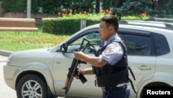 A police officer responds in Almaty after a gunman targeted police and left seven people dead.