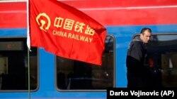 Рабочий на участке железной дороги, реконструкция которой позволит соединить Будапешт с Белградом. На флаге — логотип китайской железнодорожной компании.